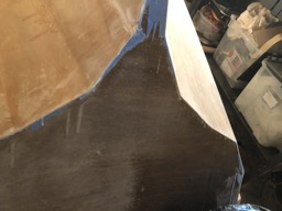 The transom is partially sanded.