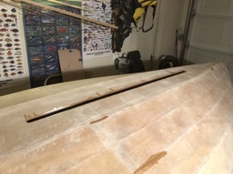The boat is flipped so the underside of the inwales can be epoxy coated. View of the centerboard hole here.