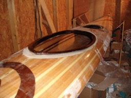 The extra fiberglass is trimmed and a fill coat is applied to the coaming.