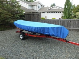 Oars, mast, daggerboard, sail, rudder, and boom fit inside boat under the cover.